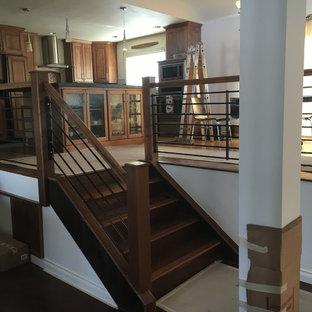 Imagen de escalera recta, rústica, de tamaño medio, con escalones de madera, contrahuellas de madera y barandilla de madera