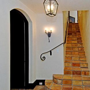 Diseño de escalera recta, mediterránea, con escalones de terracota, contrahuellas de terracota y barandilla de metal
