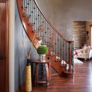 Imagen de escalera curva, clásica, de tamaño medio, con contrahuellas de madera, escalones de madera y barandilla de varios materiales