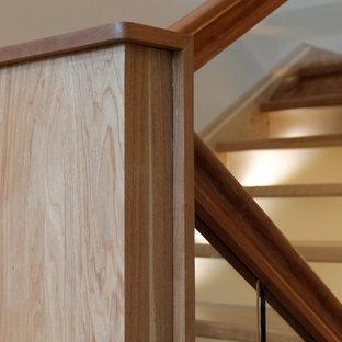 ボルチモアの大きいフローリングのコンテンポラリースタイルのおしゃれな折り返し階段 (ガラスの蹴込み板、木材の手すり) の写真