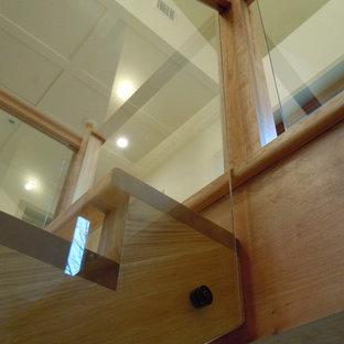 ボルチモアの大きいフローリングのラスティックスタイルのおしゃれな折り返し階段 (ガラスの蹴込み板、木材の手すり) の写真