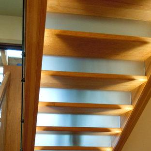 Imagen de escalera en U, rústica, grande, con escalones de madera pintada, contrahuellas de vidrio y barandilla de madera
