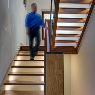 ボルチモアの大きいフローリングのコンテンポラリースタイルのおしゃれな折り返し階段 (木材の手すり、ガラスの蹴込み板) の写真