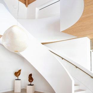 Diseño de escalera curva, contemporánea, grande, con escalones de piedra caliza y contrahuellas de piedra caliza