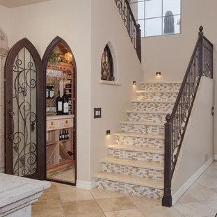 Diseño de escalera en U, mediterránea, de tamaño medio, con contrahuellas con baldosas y/o azulejos, escalones de travertino y barandilla de metal
