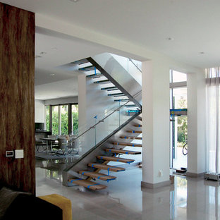 Стильный дизайн: огромная лестница на больцах в современном стиле с стеклянными ступенями без подступенок - последний тренд