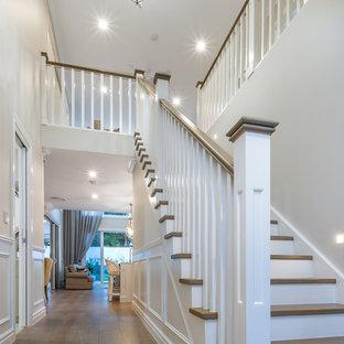 Diseño de escalera recta, clásica, de tamaño medio, con escalones de madera, contrahuellas de travertino y barandilla de madera