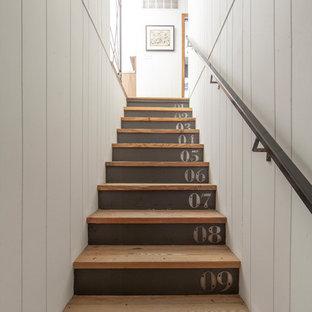Diseño de escalera recta, de estilo de casa de campo, con escalones de madera y barandilla de metal