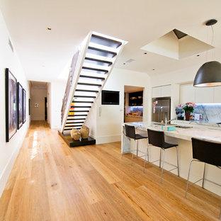 Immagine di una scala a chiocciola minimalista di medie dimensioni con pedata in legno e nessuna alzata