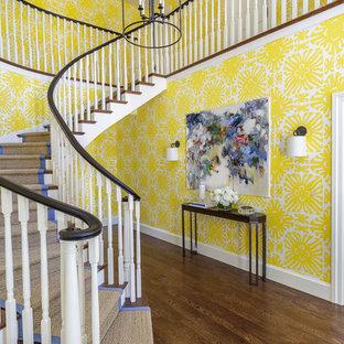 Exempel på en klassisk svängd trappa, med heltäckningsmatta, sättsteg med heltäckningsmatta och räcke i trä