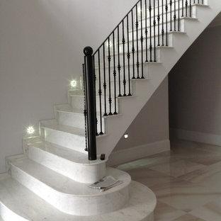 他の地域の大理石のコンテンポラリースタイルのおしゃれな直階段 (大理石の蹴込み板、金属の手すり) の写真