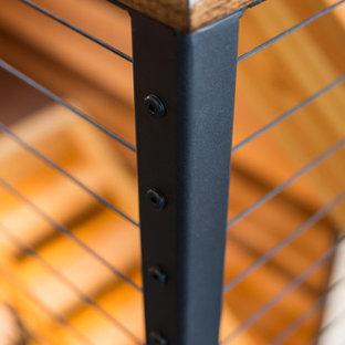 """Idee per una grande scala a """"U"""" stile rurale con pedata in legno, nessuna alzata e parapetto in cavi"""