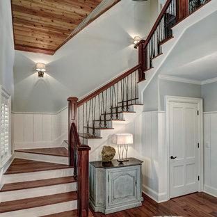 На фото: п-образная лестница среднего размера в классическом стиле с деревянными ступенями, крашенными деревянными подступенками и перилами из смешанных материалов