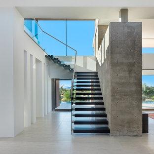 Imagen de escalera suspendida, moderna, grande, sin contrahuella, con escalones de madera y barandilla de vidrio