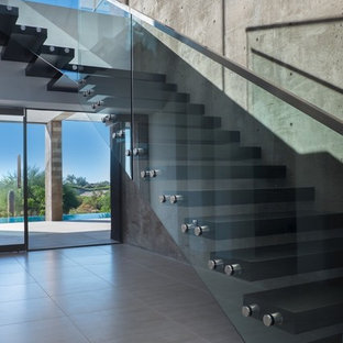 Large minimalist wooden floating open and glass railing staircase photo in Phoenix