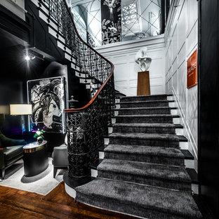 ニューヨークの巨大なフローリングのエクレクティックスタイルのおしゃれなかね折れ階段 (フローリングの蹴込み板、金属の手すり) の写真