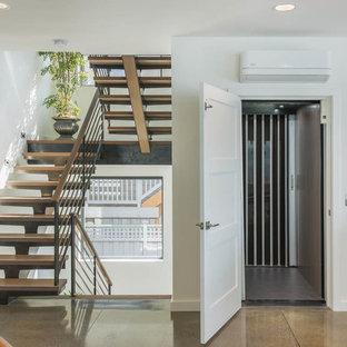 Imagen de escalera en U, contemporánea, de tamaño medio, sin contrahuella, con escalones de madera y barandilla de metal