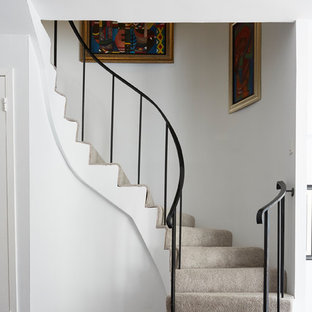 Transitional carpeted curved metal railing staircase photo in New York