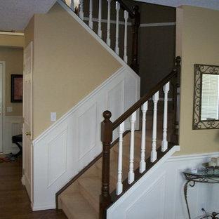カルガリーの小さいカーペット敷きのトラディショナルスタイルのおしゃれな折り返し階段 (木の蹴込み板) の写真