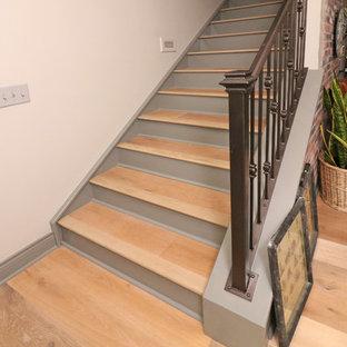 Imagen de escalera en L, escandinava, con contrahuellas de madera pintada y barandilla de metal