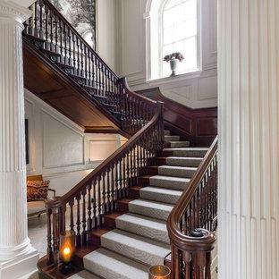 Пример оригинального дизайна: большая изогнутая лестница в классическом стиле с ступенями с ковровым покрытием, ковровыми подступенками и деревянными перилами