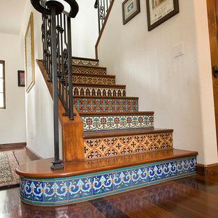 Diseño de escalera recta, de estilo americano, de tamaño medio, con escalones de madera y contrahuellas con baldosas y/o azulejos