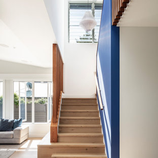Design ideas for a beach style wood u-shaped staircase in Sydney with wood risers and wood railing.