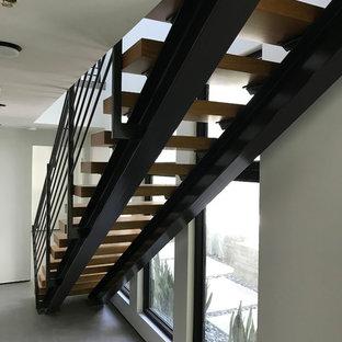 Diseño de escalera suspendida, moderna, grande, con escalones de madera y barandilla de metal