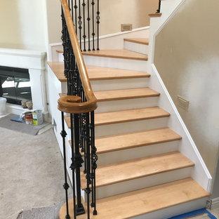 Exempel på en mellanstor klassisk svängd trappa i trä, med sättsteg i travertin och räcke i flera material