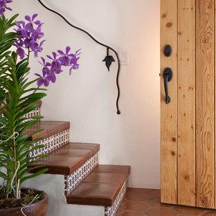 Foto de escalera mediterránea con contrahuellas con baldosas y/o azulejos, escalones de terracota y barandilla de metal