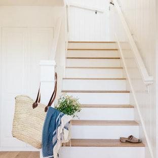Diseño de escalera en L, costera, con escalones de madera, contrahuellas de madera y barandilla de madera