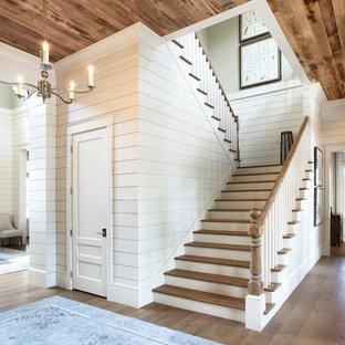 """Immagine di un'ampia scala a """"U"""" tradizionale con pedata in legno e alzata in legno verniciato"""