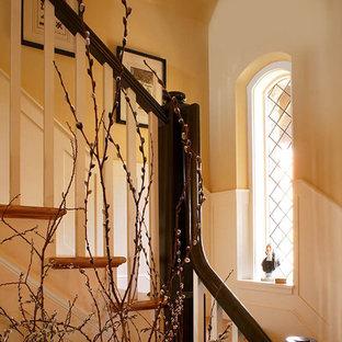 Esempio di una scala curva classica di medie dimensioni con pedata in legno, alzata in legno e parapetto in legno