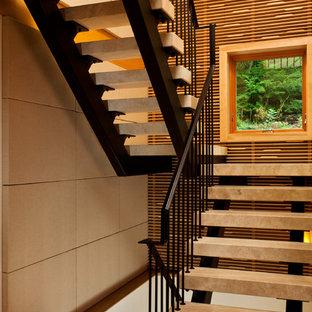 Idéer för funkis u-trappor i travertin, med öppna sättsteg och räcke i metall