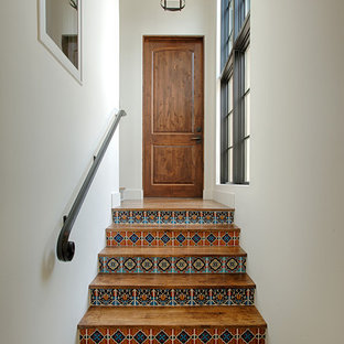 Mediterranean wood straight staircase in Austin with tile risers and metal railing.