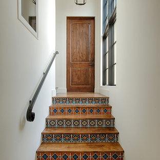 Ispirazione per una scala a rampa dritta mediterranea con pedata in legno, alzata piastrellata e parapetto in metallo