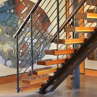 Ispirazione per una piccola scala a rampa dritta industriale con pedata in legno, alzata in legno e parapetto in metallo