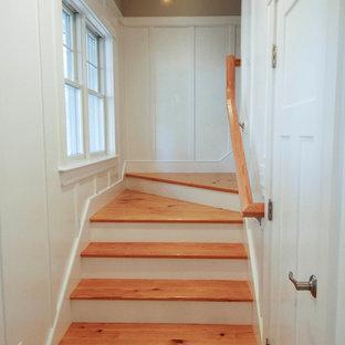 Ejemplo de escalera en L, de estilo americano, de tamaño medio, con escalones de madera, contrahuellas de madera pintada y barandilla de madera