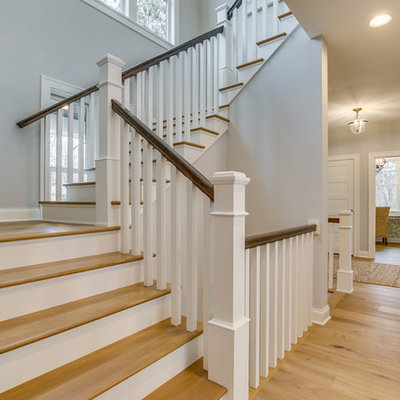 Example of a mid-sized farmhouse wooden u-shaped wood railing staircase design in Minneapolis with painted risers