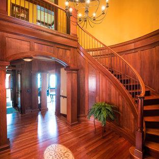 ミネアポリスの中サイズの木のトラディショナルスタイルのおしゃれなサーキュラー階段 (木の蹴込み板、木材の手すり) の写真