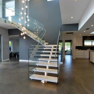 Foto de escalera en L, moderna, de tamaño medio, sin contrahuella, con escalones de mármol y barandilla de metal