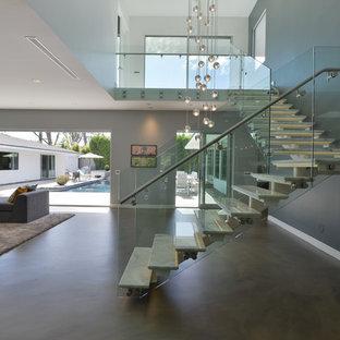 Foto de escalera en L, minimalista, de tamaño medio, sin contrahuella, con escalones de mármol y barandilla de vidrio