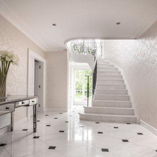 Ispirazione per una grande scala curva tradizionale con pedata in marmo, alzata in marmo e parapetto in metallo