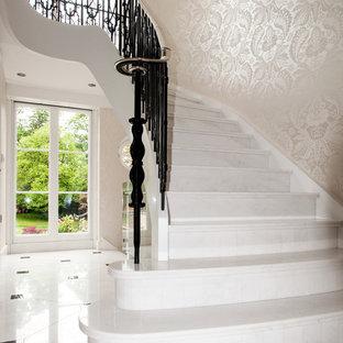 Idéer för att renovera en stor vintage svängd trappa i marmor, med sättsteg i marmor och räcke i metall
