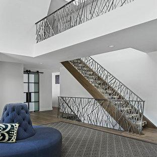 Exempel på en stor modern rak trappa i marmor, med öppna sättsteg och räcke i metall