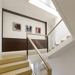 """Immagine di una scala a """"U"""" moderna con parapetto in vetro"""