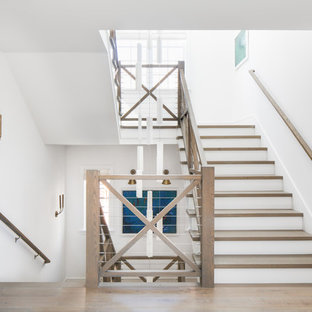 Beach style wood u-shaped staircase in Los Angeles with painted wood risers and cable railing.