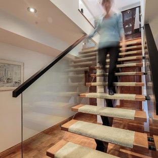 Idee per una scala sospesa contemporanea di medie dimensioni con pedata in legno, nessuna alzata e parapetto in vetro