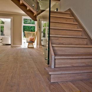 Foto de escalera en L, rural, de tamaño medio, con escalones de madera, contrahuellas de madera y barandilla de vidrio