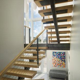 Imagen de escalera suspendida, contemporánea, pequeña, sin contrahuella, con escalones de madera y barandilla de metal